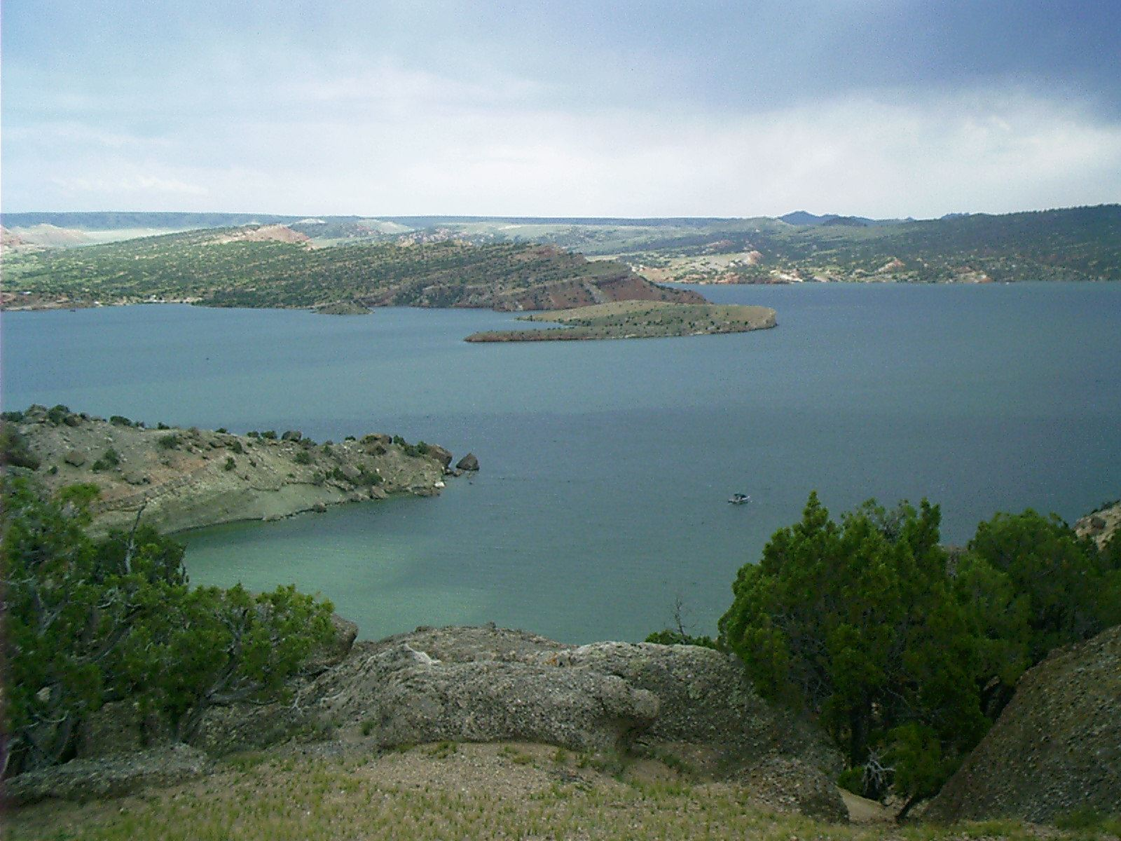 trees and rocks overlooking Alcova Reservoir, blue water, hills with trees